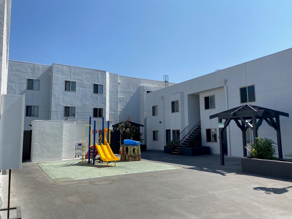 Exterior view of a common area with a playground at Harmony Gates Apartments