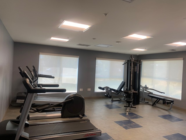 View of a small gym, workout equipment, three windows with white shades, linoleum floors.