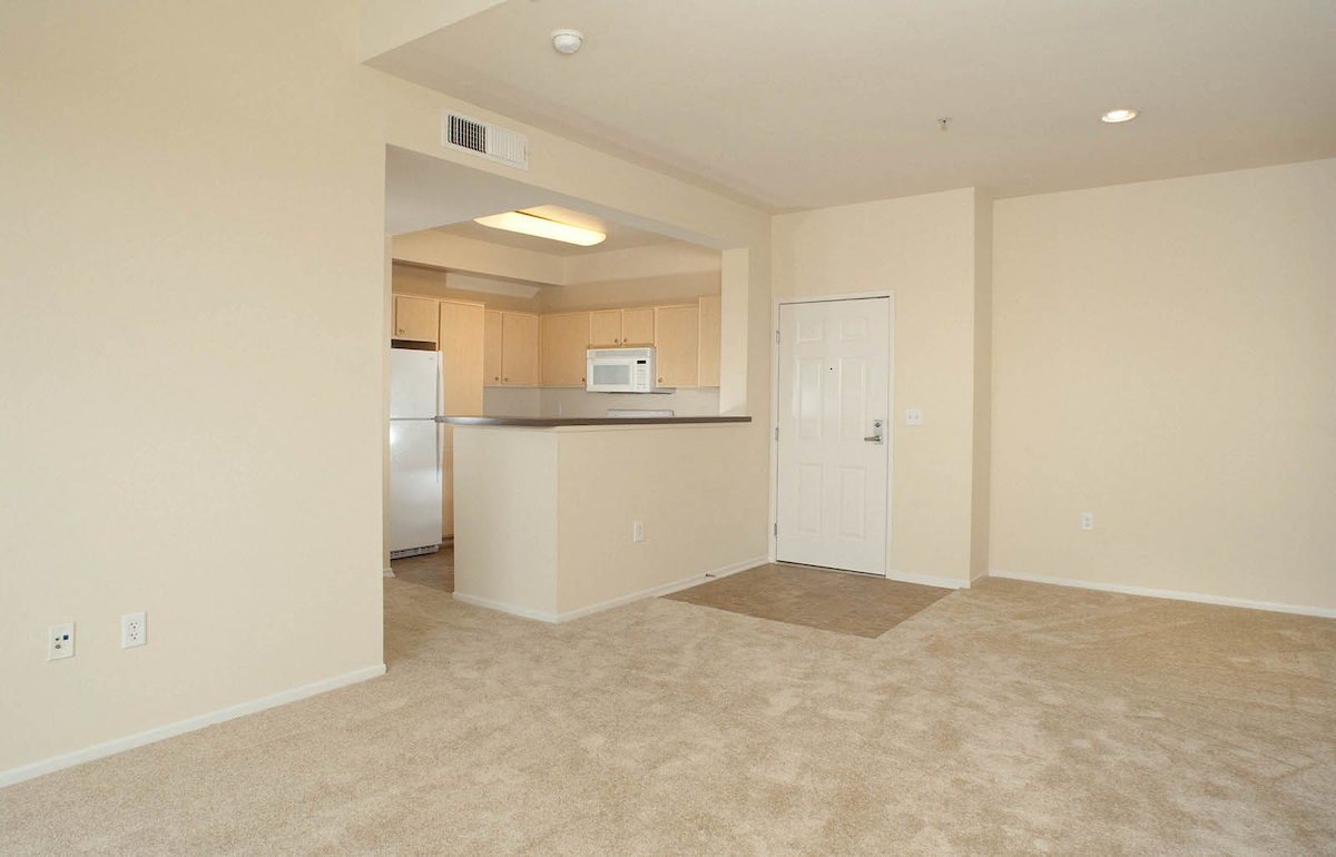 sample of Fountain Park unit living room area. white carpets, access to kitchen near front door.