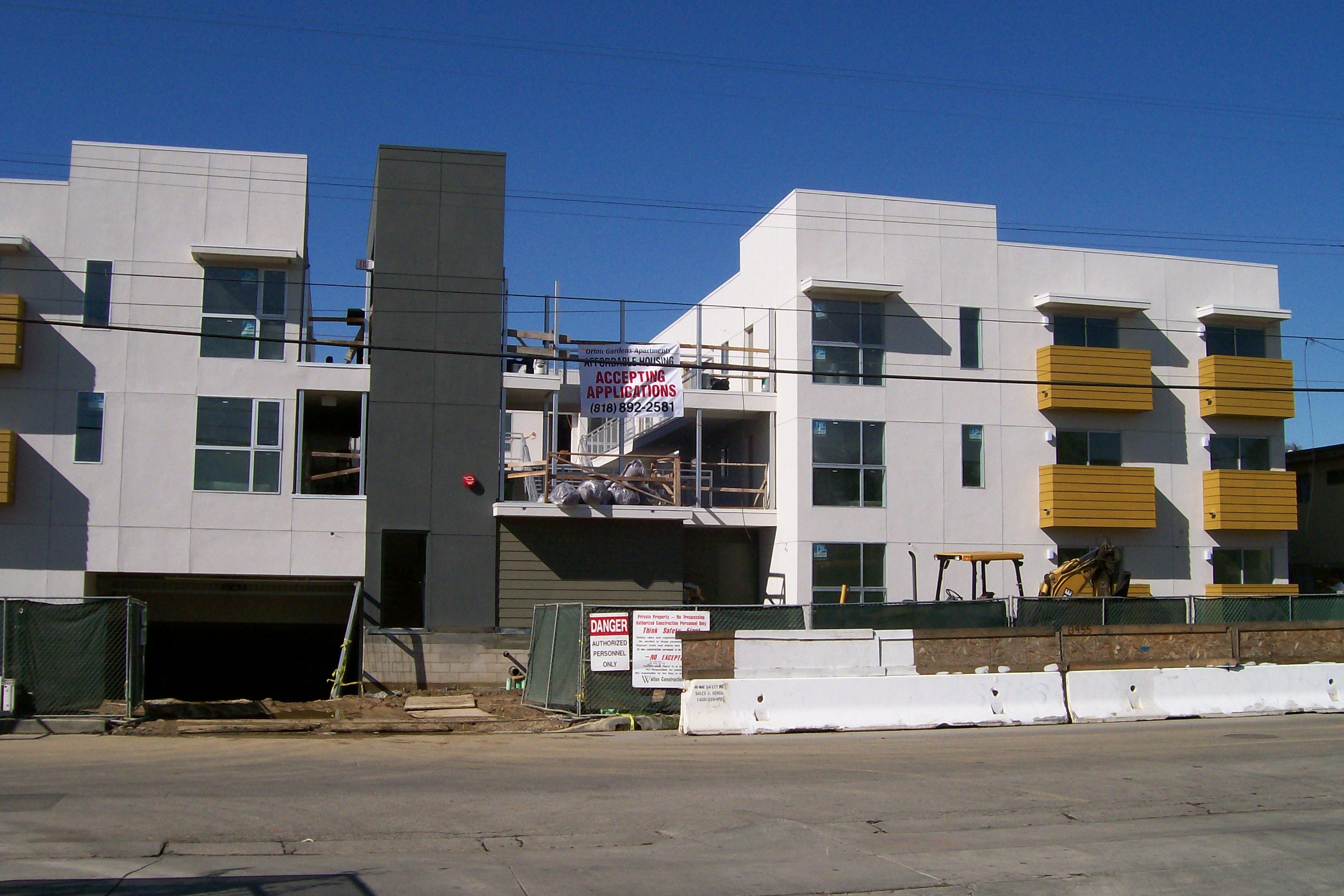 Front view of a white half way in construction building, mustard color balconies, yellow bulldozer, Affordable Housing sign Accepting apllications big white sign hanging, chicken wire fence with Danger sign.