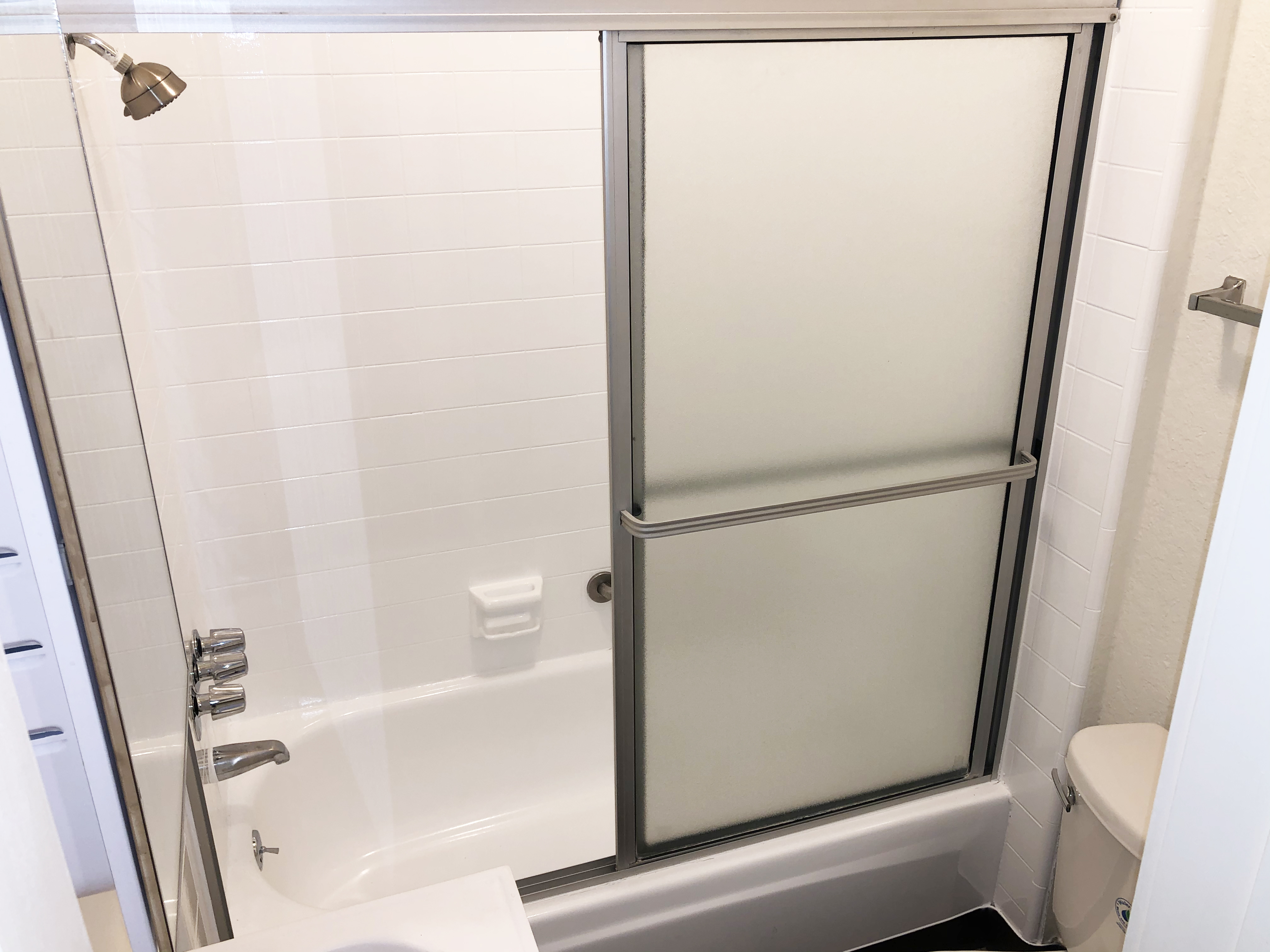 Close up view of the restroom showing the bathtub with showing and sliding door