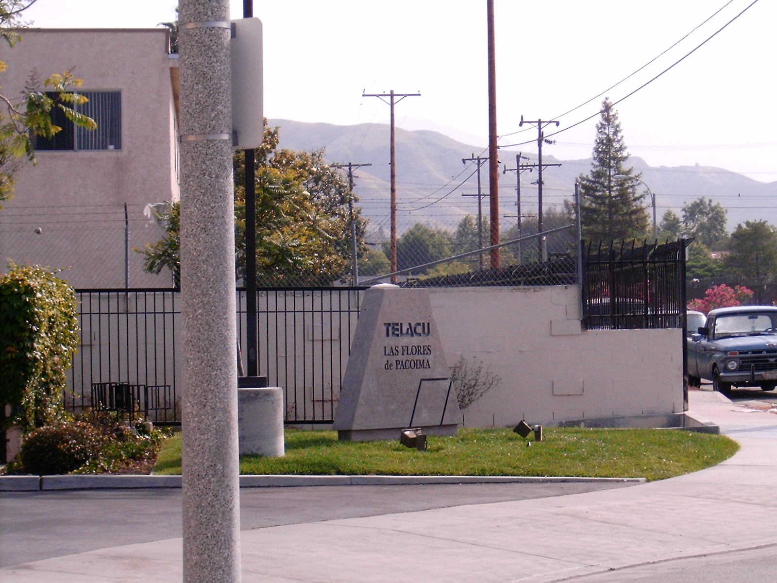 "Corner view of the building, concrete standing stone with the building's name ""Telacu Las Flores de Pacoima"", old blue parked truck, grass and plants in front of the gated building."