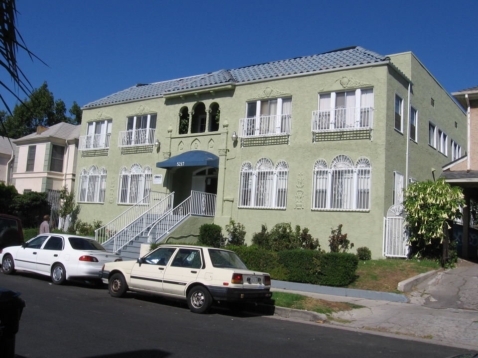 Street view of one story building in green color with white railing and windows. Front entrance through stairs