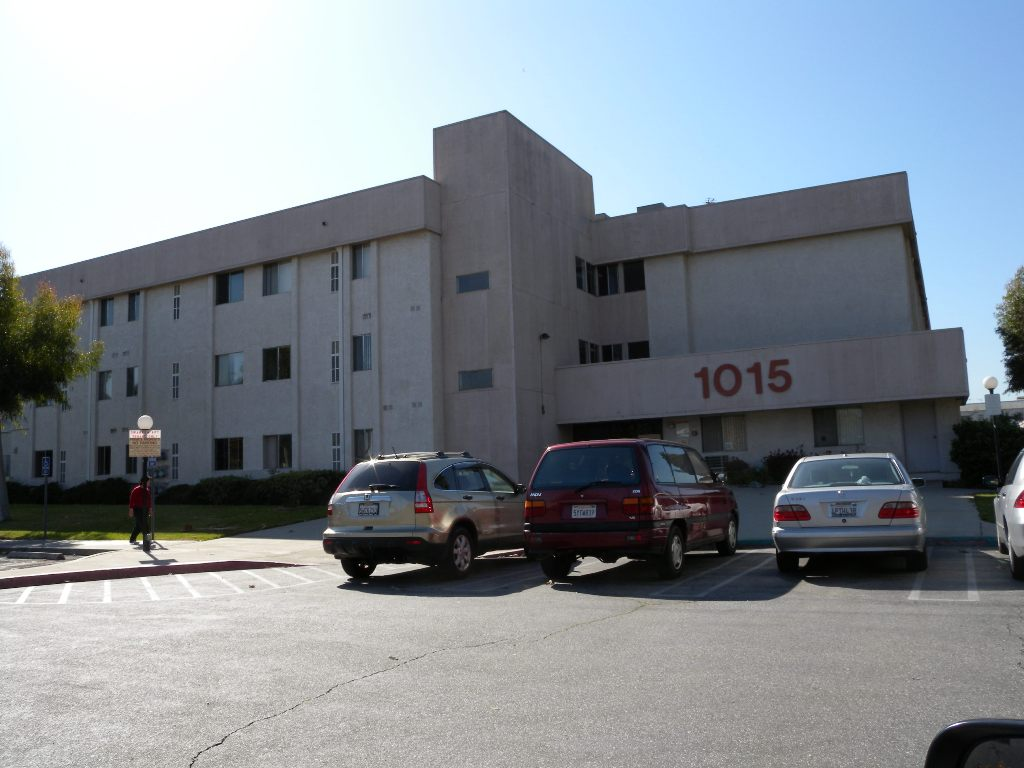 Three story building with accessible entry way and adjacent open parking.