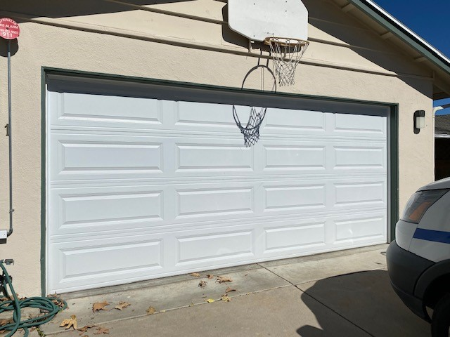 Close up view of garage door with basketball hoop above the door and light fixtures on one side.
