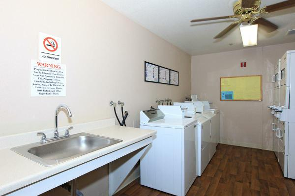 Side view of a laundry room, a sink and four white washer on the left side, beige walls and white ceiling, ceiling fan, four white dryers on the right side, a board with flyers, no smoking and warnings signs on the left side wall.