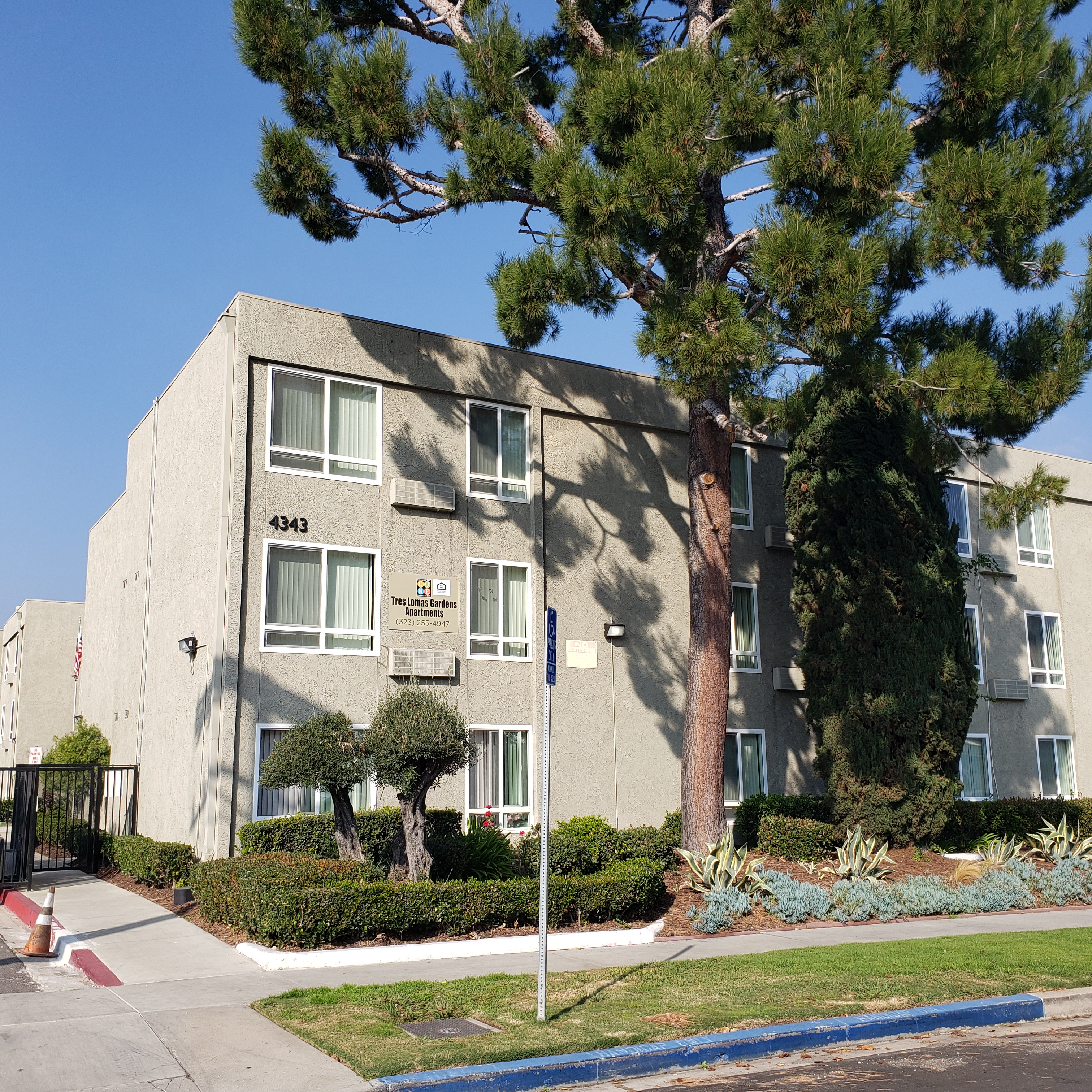 Front view of tres lomas garden apartments. multi-story building with large trees, bushes and grass in the front. Section of curb on street is painted blue with parking accessibility sign.