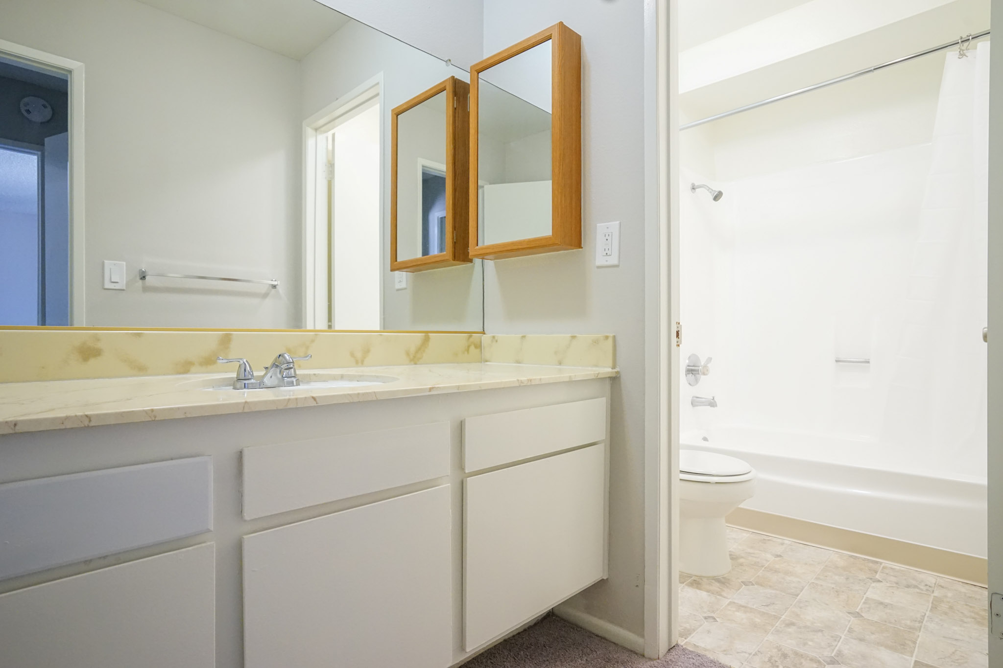 View of a bathroom with a sink, mirror, medicine cabinet, toilet and a bathtub. There are cabinets under the sink, and towel rack across from it.
