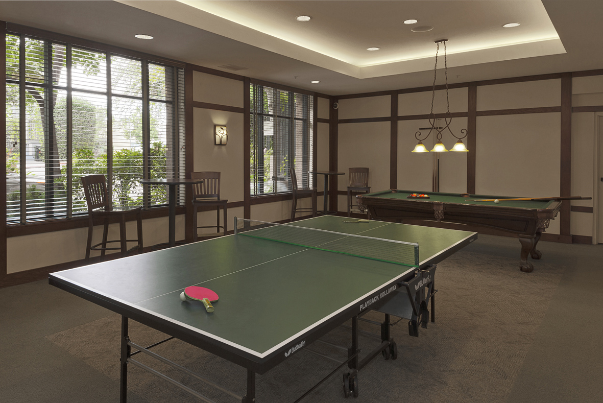 Common room that consists of a pool table and a ping pong table. There are a couple of high chairs and high tables. Room has large windows with horizontal blinds.