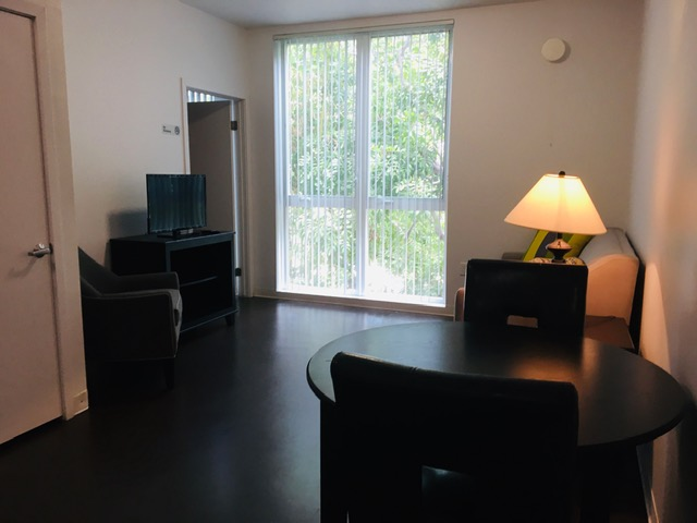View of a unit, dark brown wood floors, small black round table with two chairs, other couches, a TV, a window with white vertical blinds.