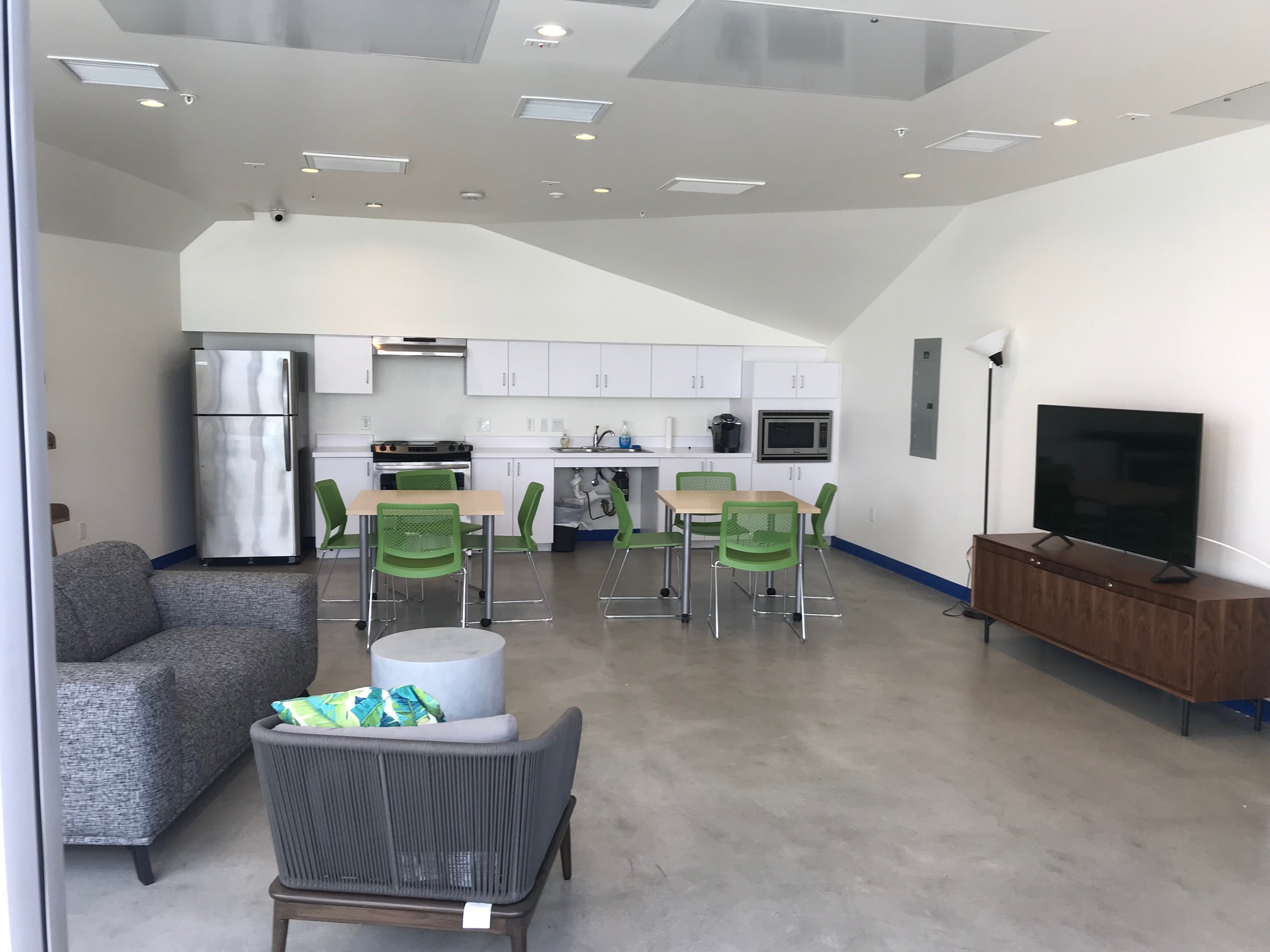 Interior view of a community room at King 1101 Apartments showing couches, tables, television and a kitchen area with a refigerator, stove, sink and microwave.