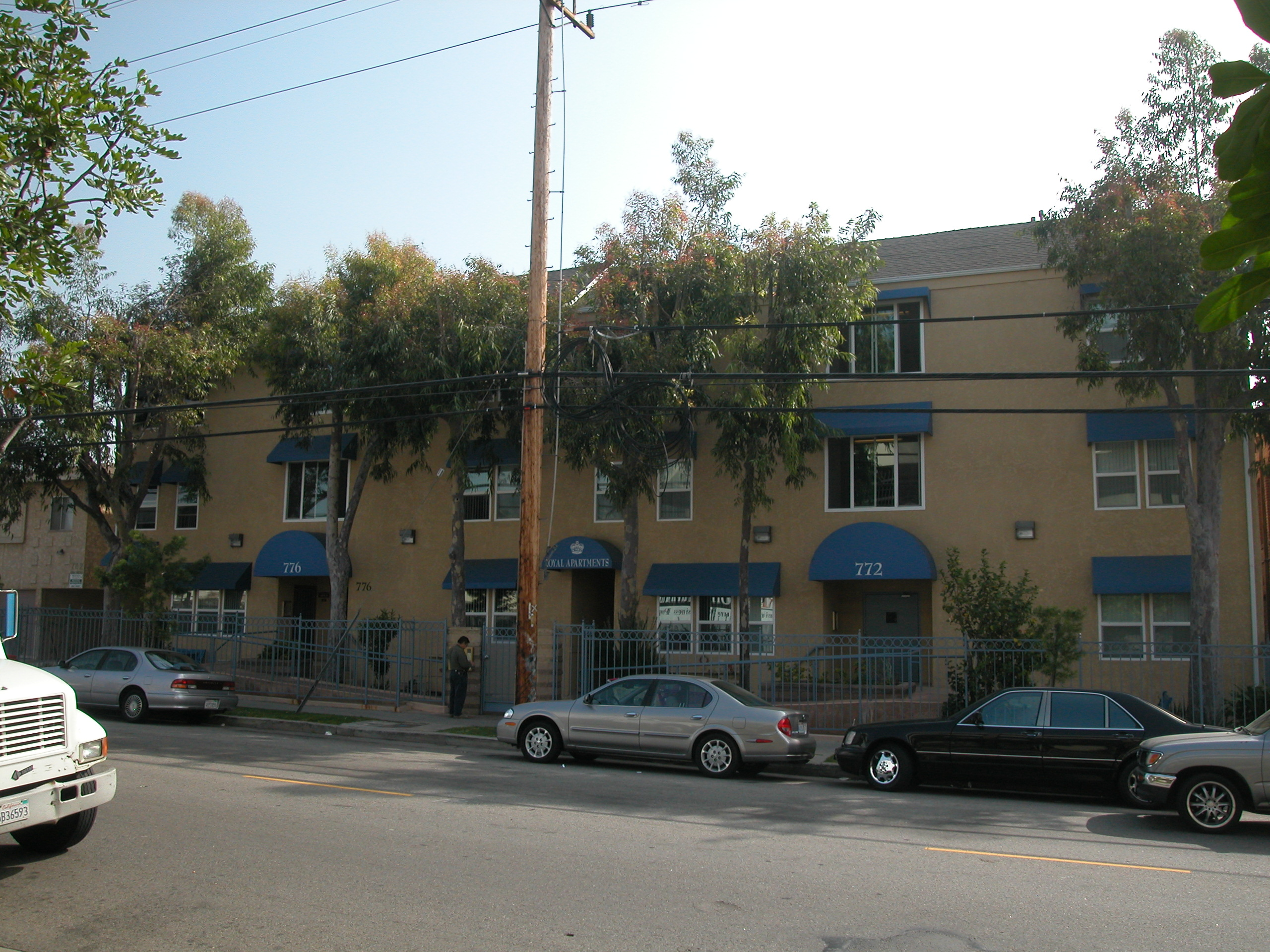 Brown-Yellowish, three story building with blue shades in multiple windows, property number and name in bottom blue shades, gated property, parked cars in front, trees and bushes in front of property, a male getting keys ready to go in, light pole right i