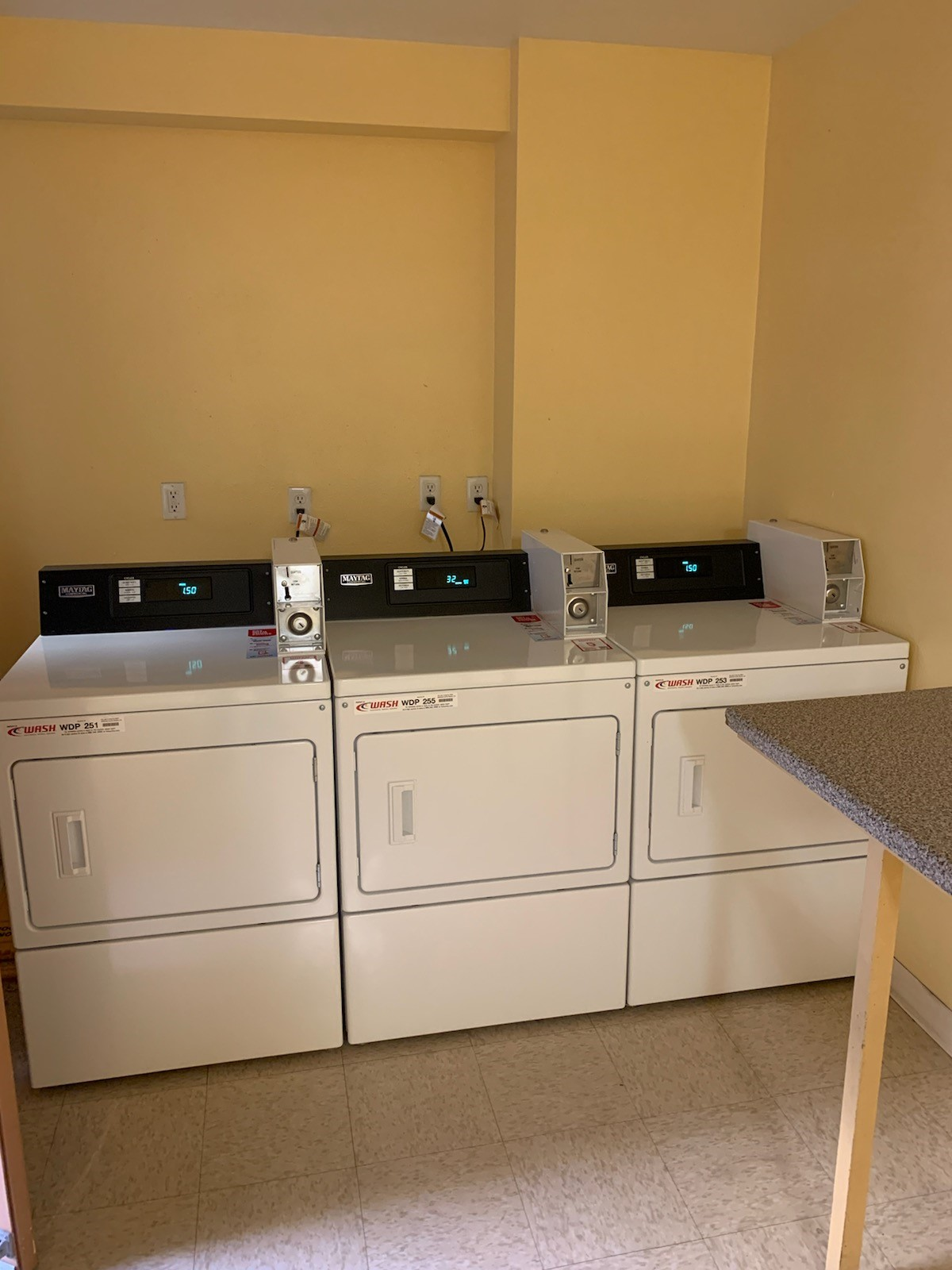 Laundry room with three machines shown and a folding table.