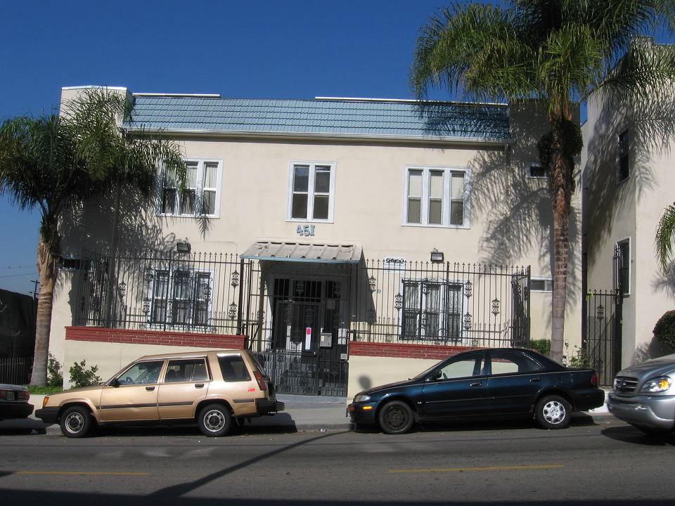 Front view of a beige two story building, multiple windows with white trim, gated building, bottom windows with security bars, gray steps toward the main entrance, call box on the right side, parked cars in front, palm trees and plants.
