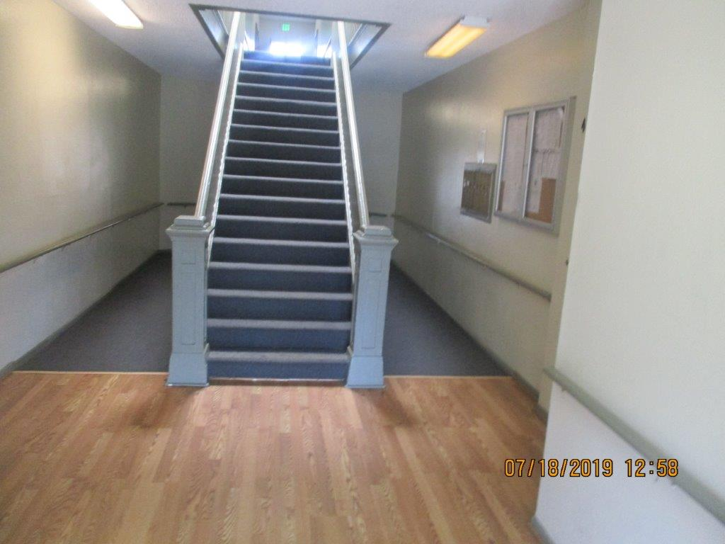 17 rugged staircase with strong wood handrails, lighted hall, half rug and other half laminate floor, to the right side a locked showcase and next to it the mailboxes.