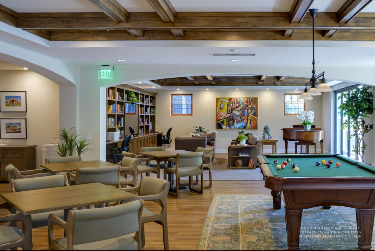 Inside view of a community room. There is a pool table, three table sets, a piano, a computer setup desk with a printer, a bookshelf full of books, and sofas. Across the room there are some plants and modern art on the walls.