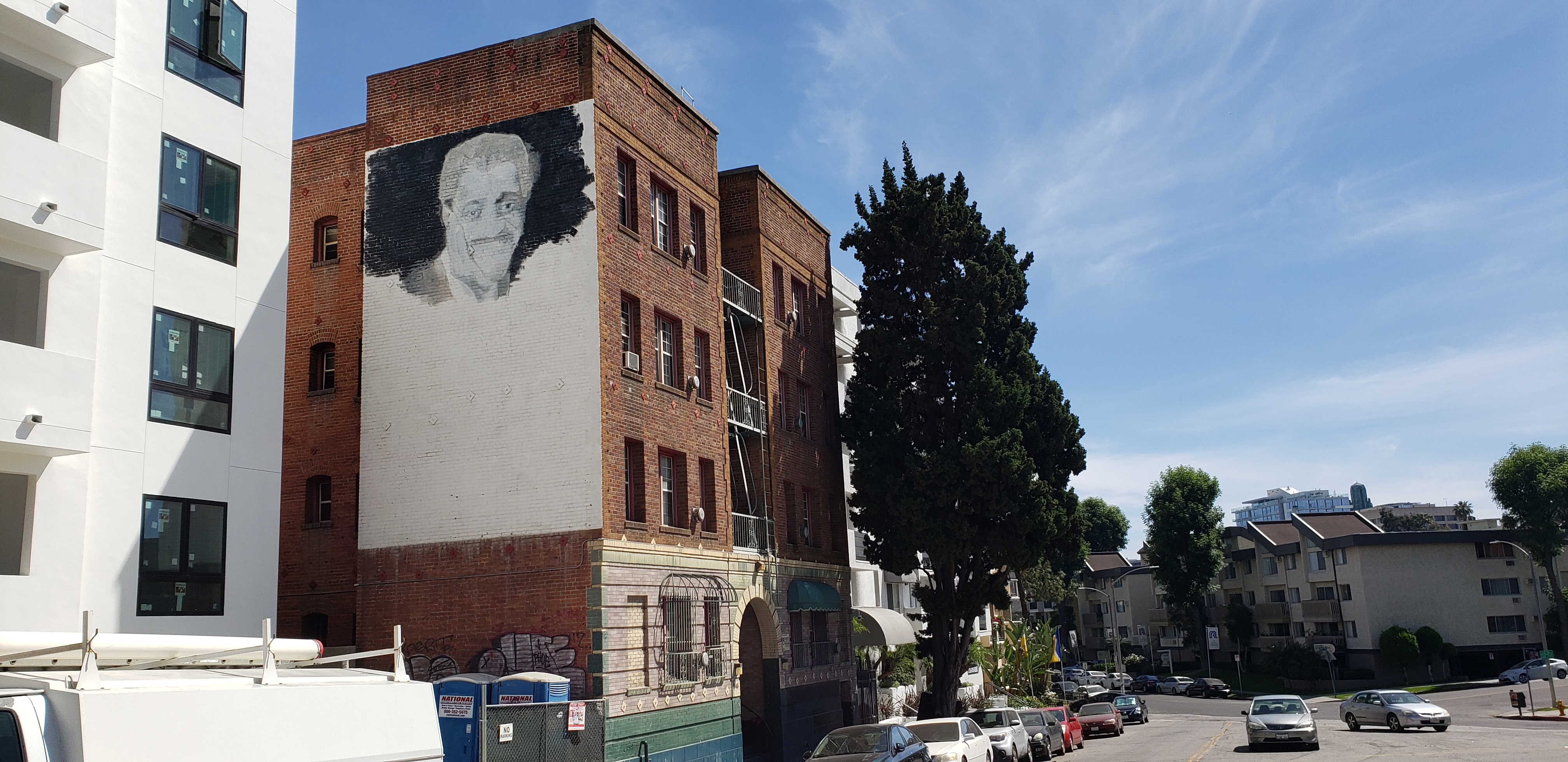Street view of Reno Apartments with an unfinished mural of Sammy Davis Jr on the side of the building and large tree in front