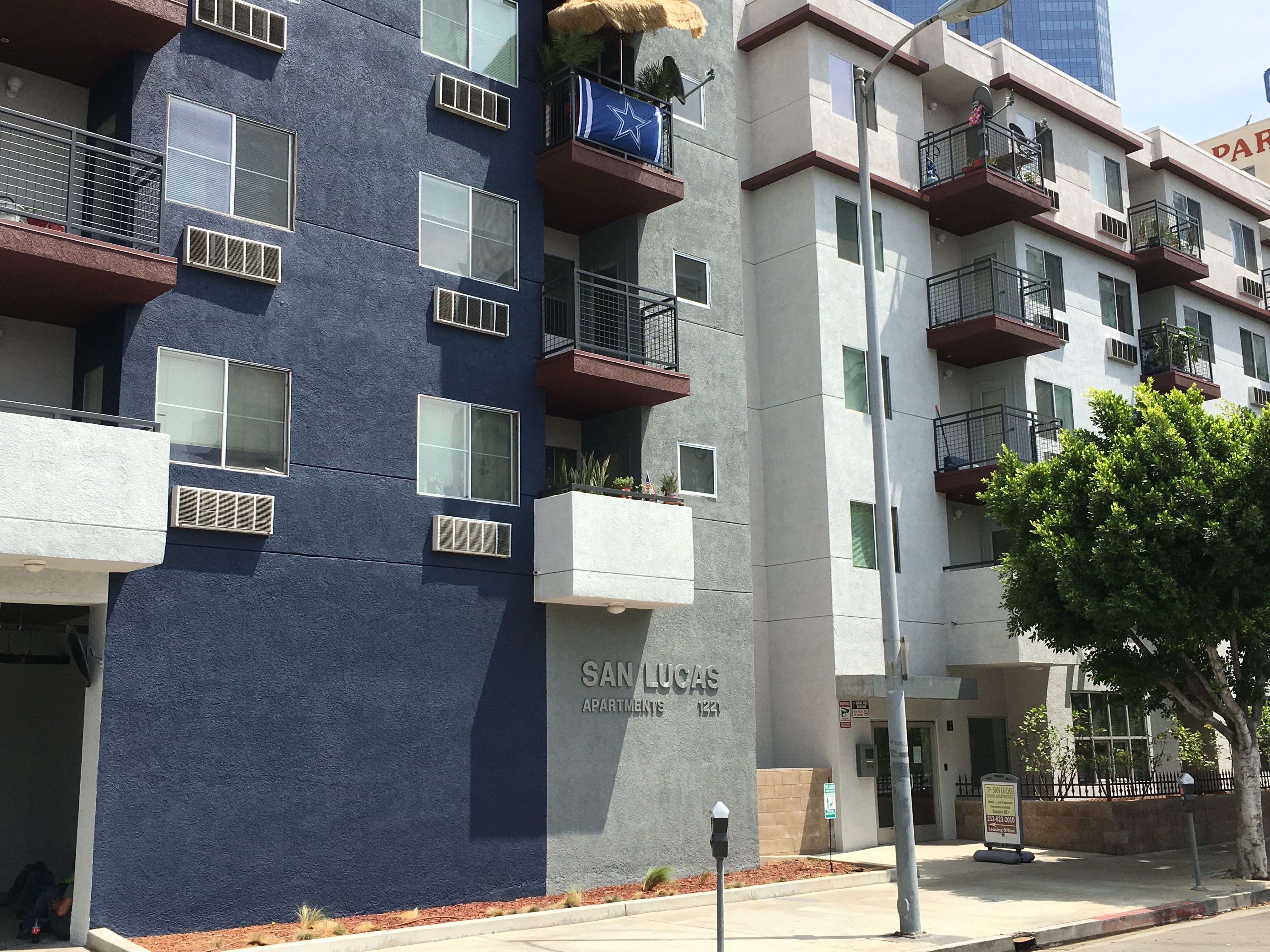 Street view of San Lucas Apartments, 5 story grey and blue building with balconies and lamp post in front