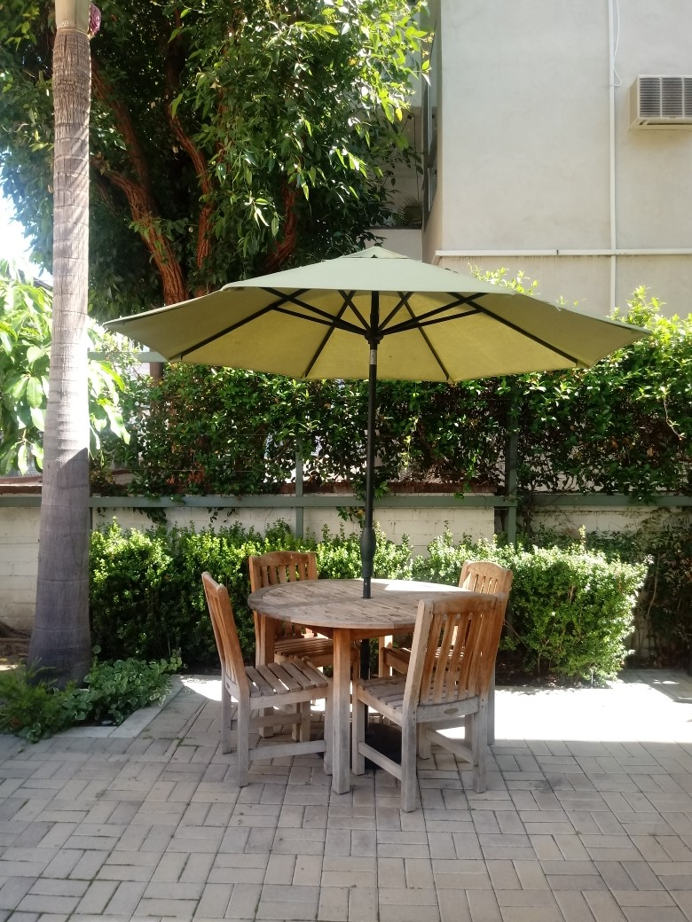 Alexandria House court yard. Patio table and four chairs with umbrella for shade. bushes located along wall