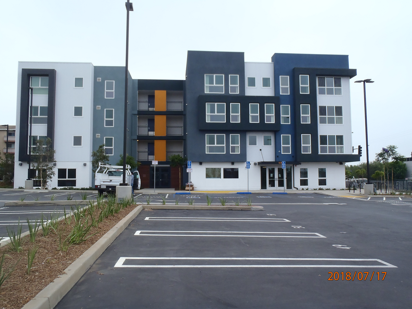Front view of 4 floor building with parking lot