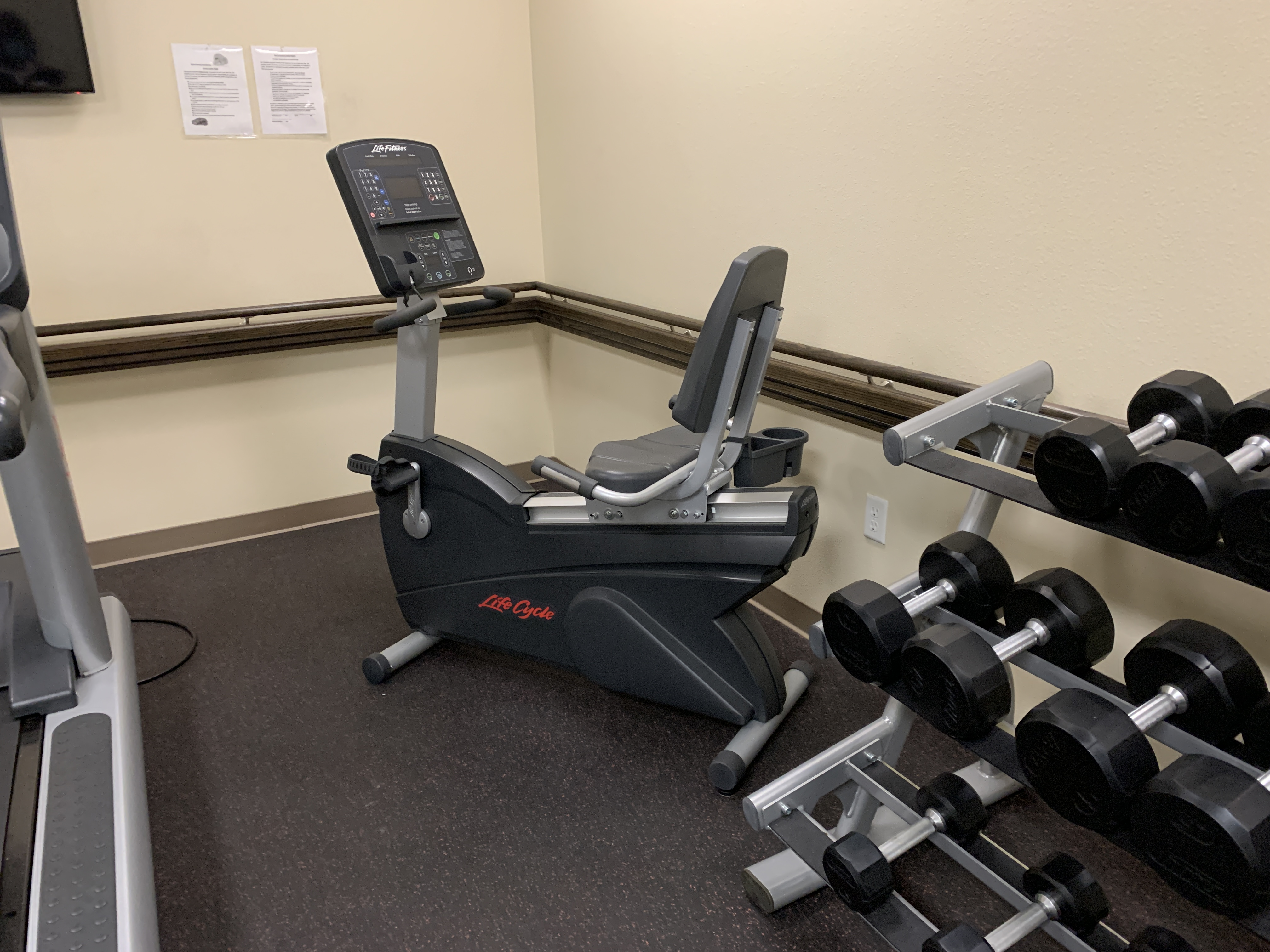 View of a corner of a fitness room. There is an exercise bike machine and weights on a stand.