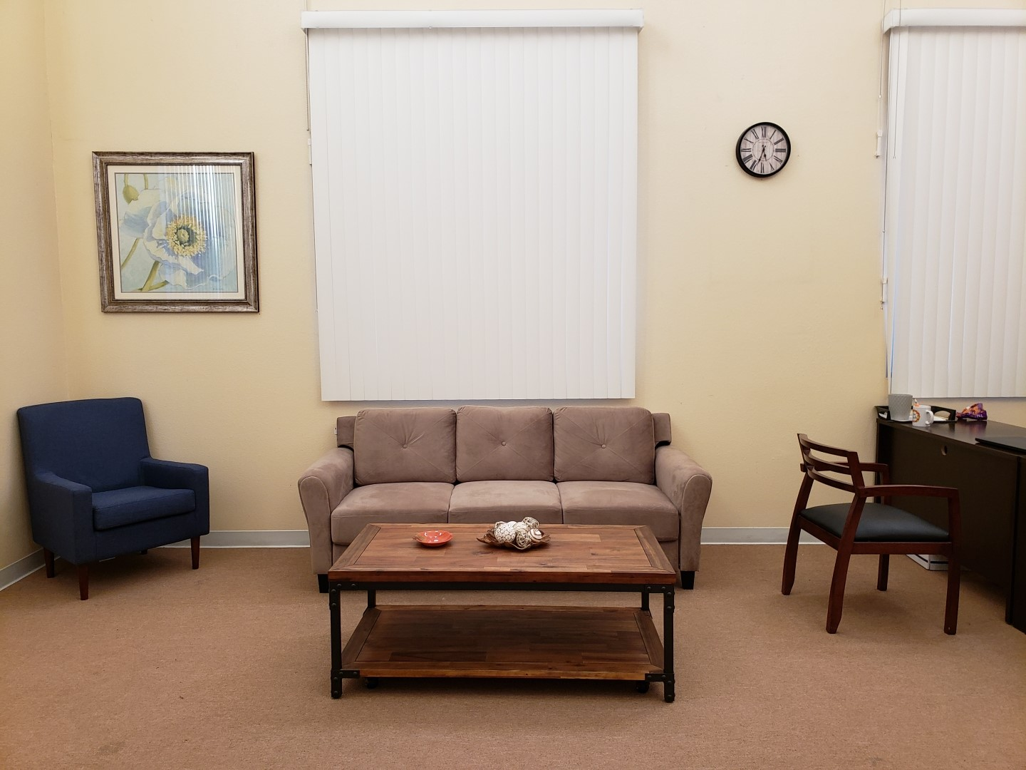 Lobby area with a sofa chair, couch, coffee table, and reception desk. There are two windows with vertical blinds. On the wall there is a clock and a painting, and the floor is carpeted.