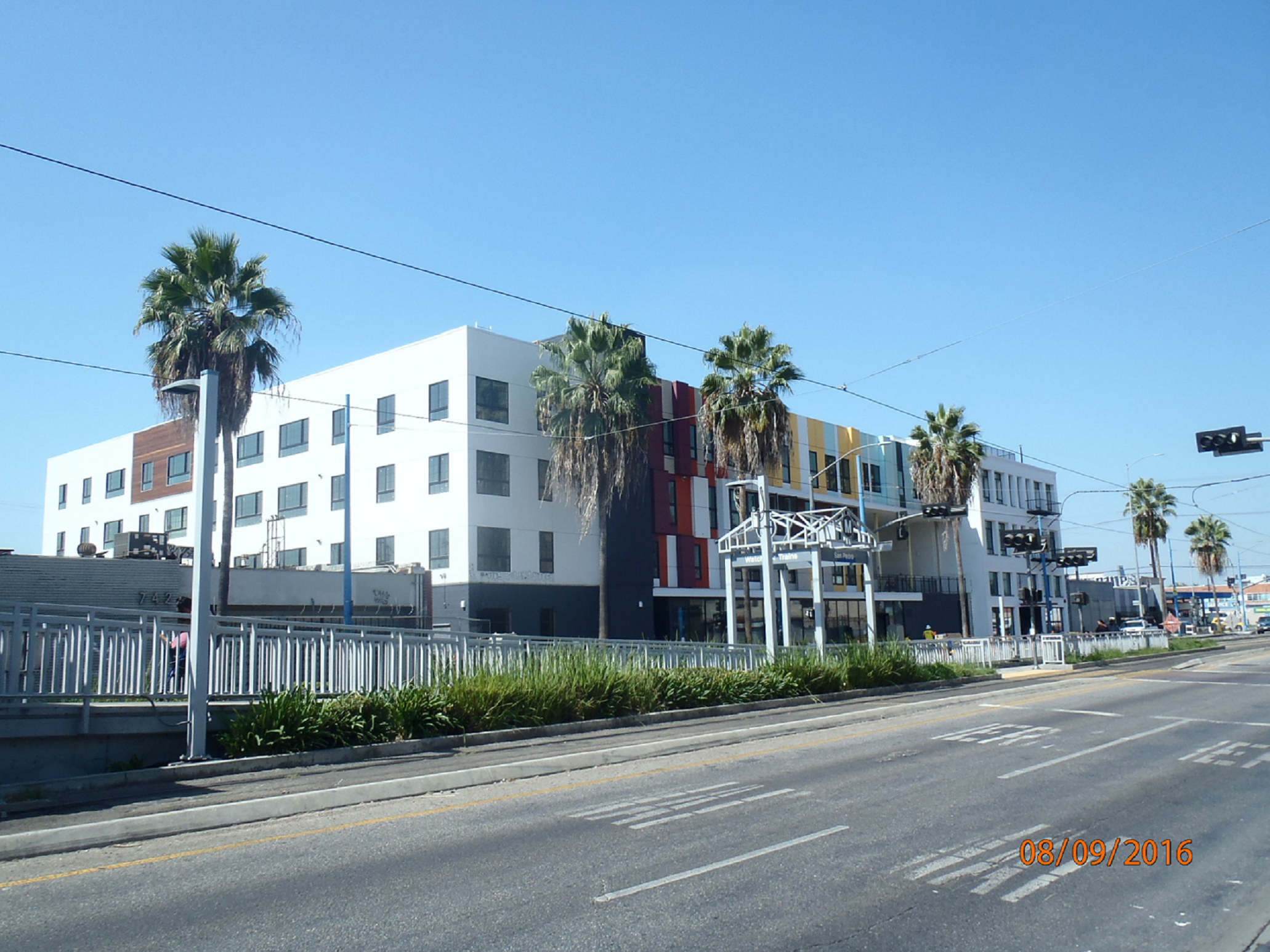 Four story white modern building with small stripes of red and yellow. Building is adjacent to a metrolink station. Entry way is ground level with tall windows. There are palm trees on the sidewalk in front of the building.