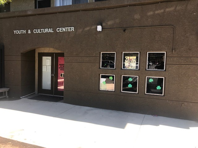 Side view of the main entrance to a Youth and Cultural Center, brown walls, double side brown and glass doors.