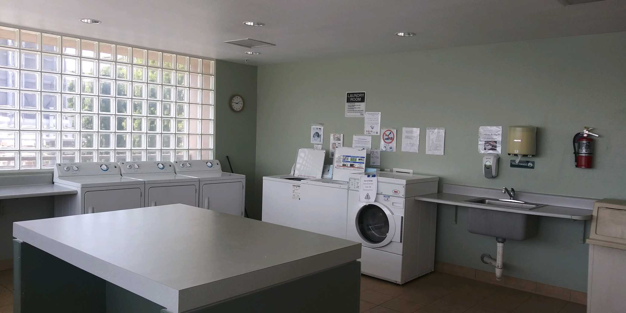 Laundry room with multiple washers and dryers. Center has a folding table. There is a large tiled window on one side of the wall. On the adjacent wall there are laundry room rules and signs posted. Thre is a sink, soap dispenser, paper towel dispenser, tr