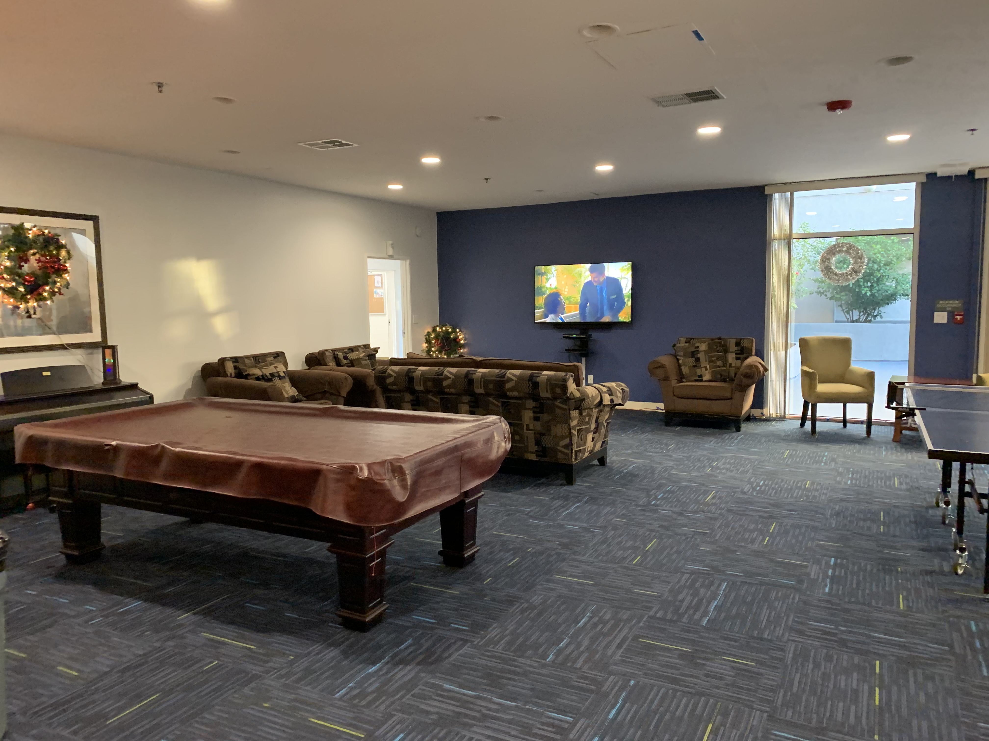 Community room that has a pool table, ping pong table, a piano, sofas, and a flat screen TV. There is a large window with vertical blinds.