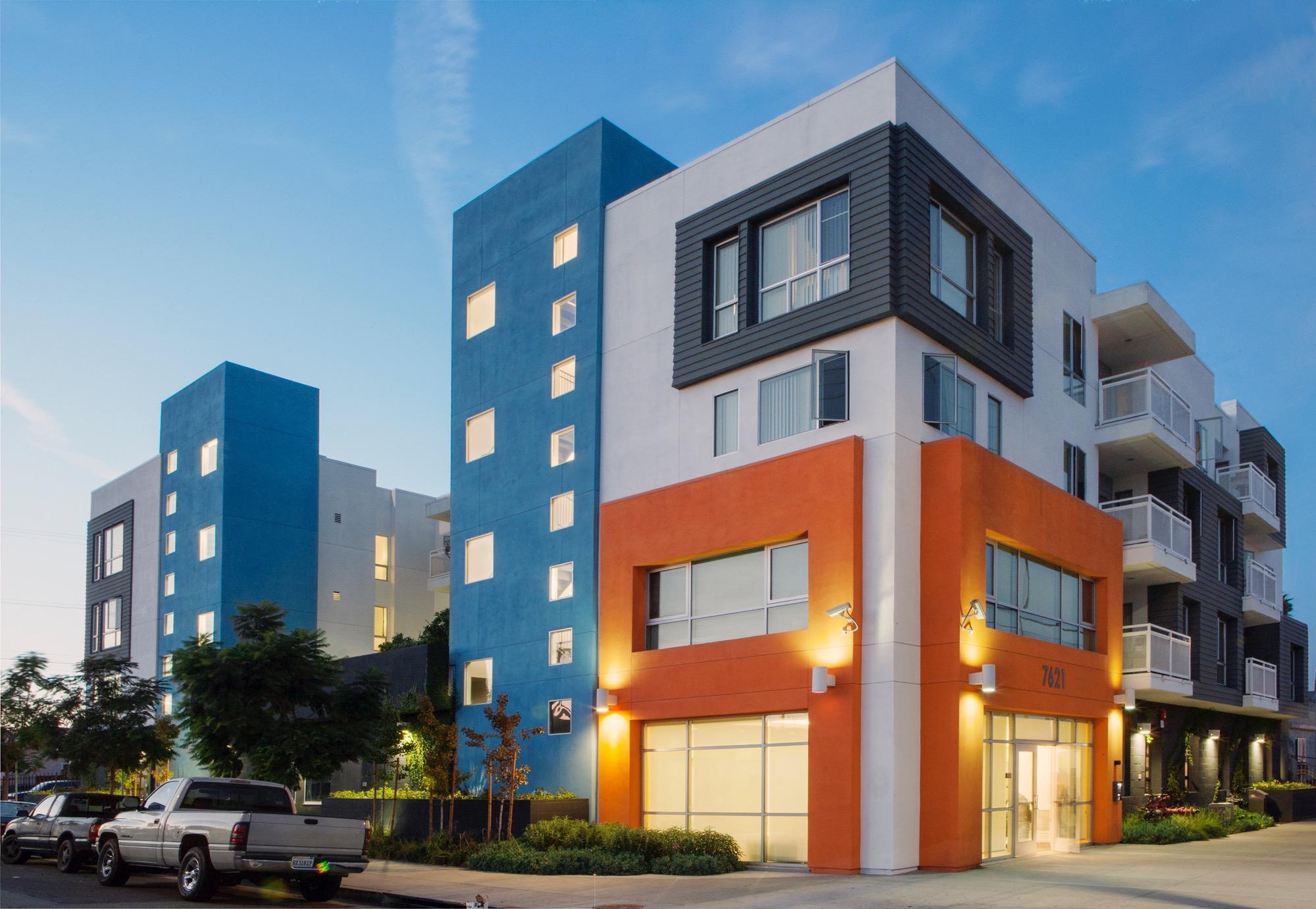 Front side view of a modern four story building. Buildong colors consist of light blue, white, gray and orange. Some units have tall windows, and some have balconies. There is newly planted trees in the front sidewalk and bushes on the side of the buildin