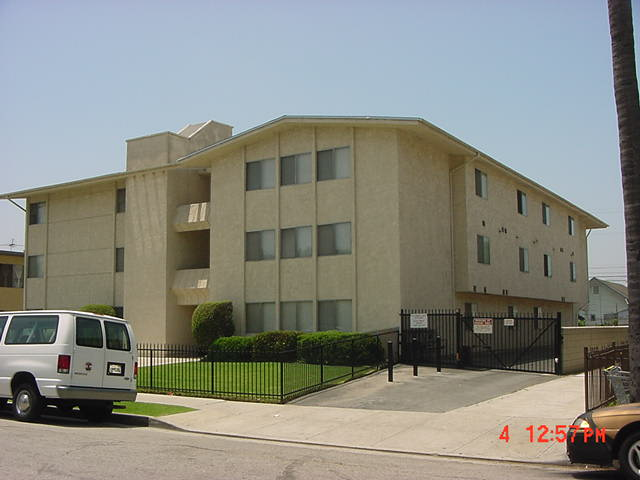 Street view of three story gated building. Gated parking area along side building. Walkway to building entrance with well kept yard