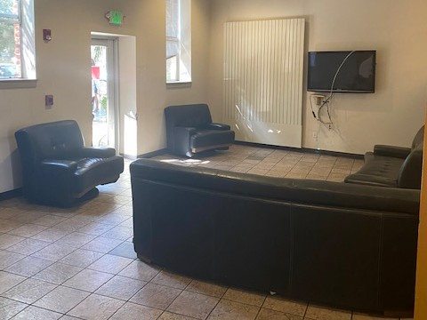 Image of the common room equipped with black couches and a tv