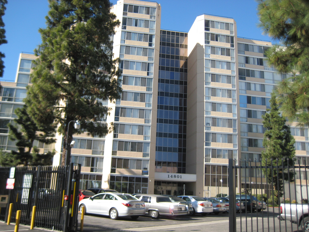 Large twelve story building with large windows. There is gated parking in front of the building.