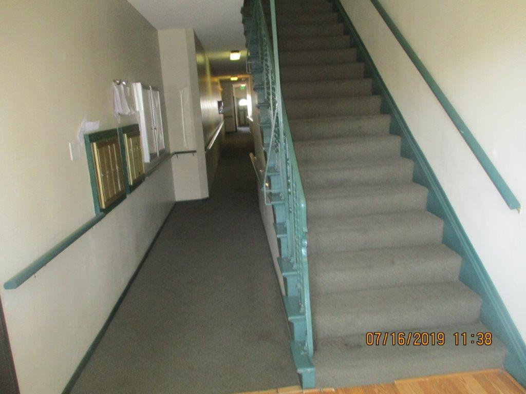 Gray carpeted well lighted inside hall, on the left side wall a locked showcase, clipboard with papers, and golden mailboxes, to the right side a long gray carpeted stairs with dark aqua color handrail.