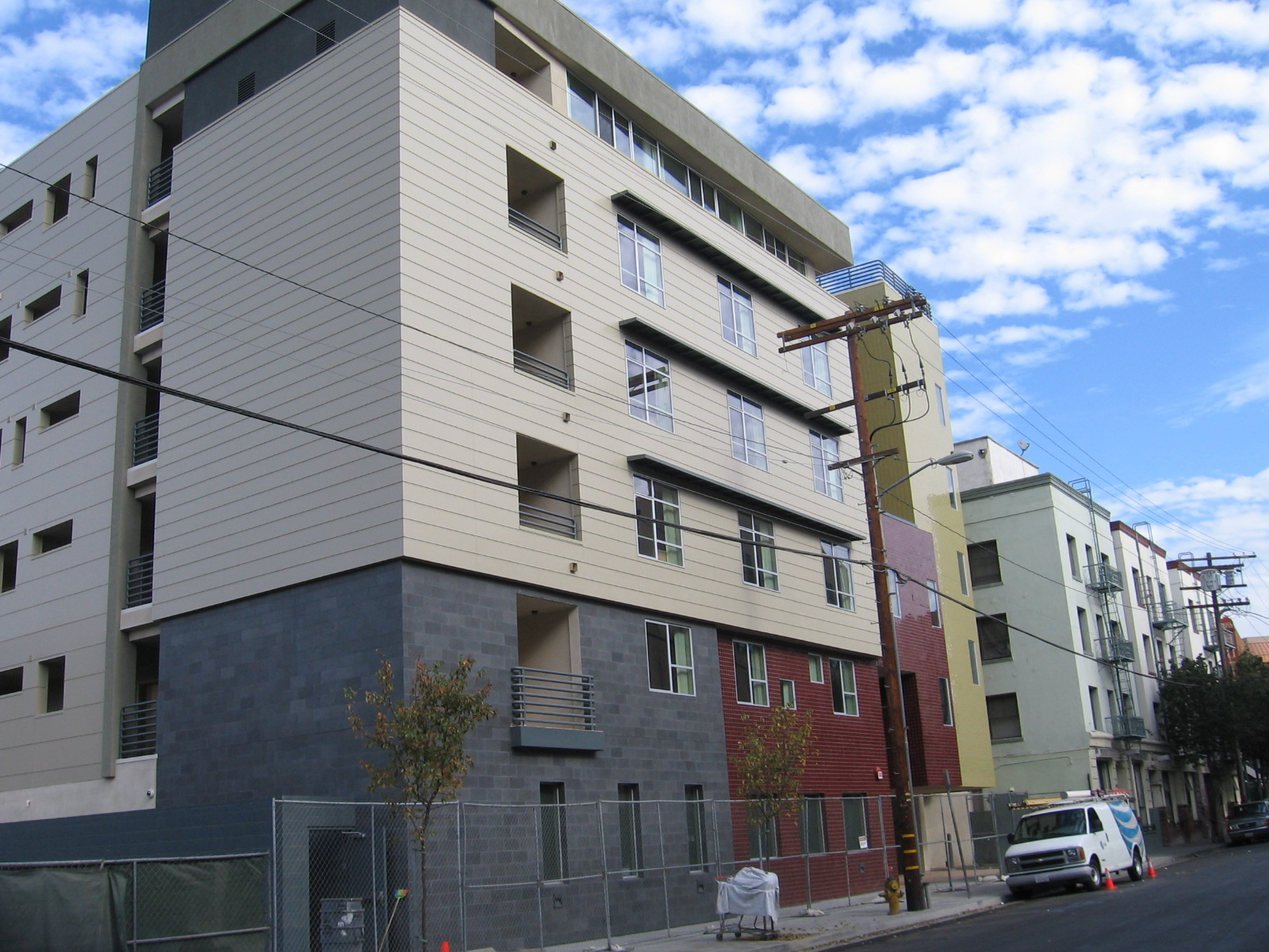 Photo of the Street view of a five story building in gold, brown and gray colors with windows