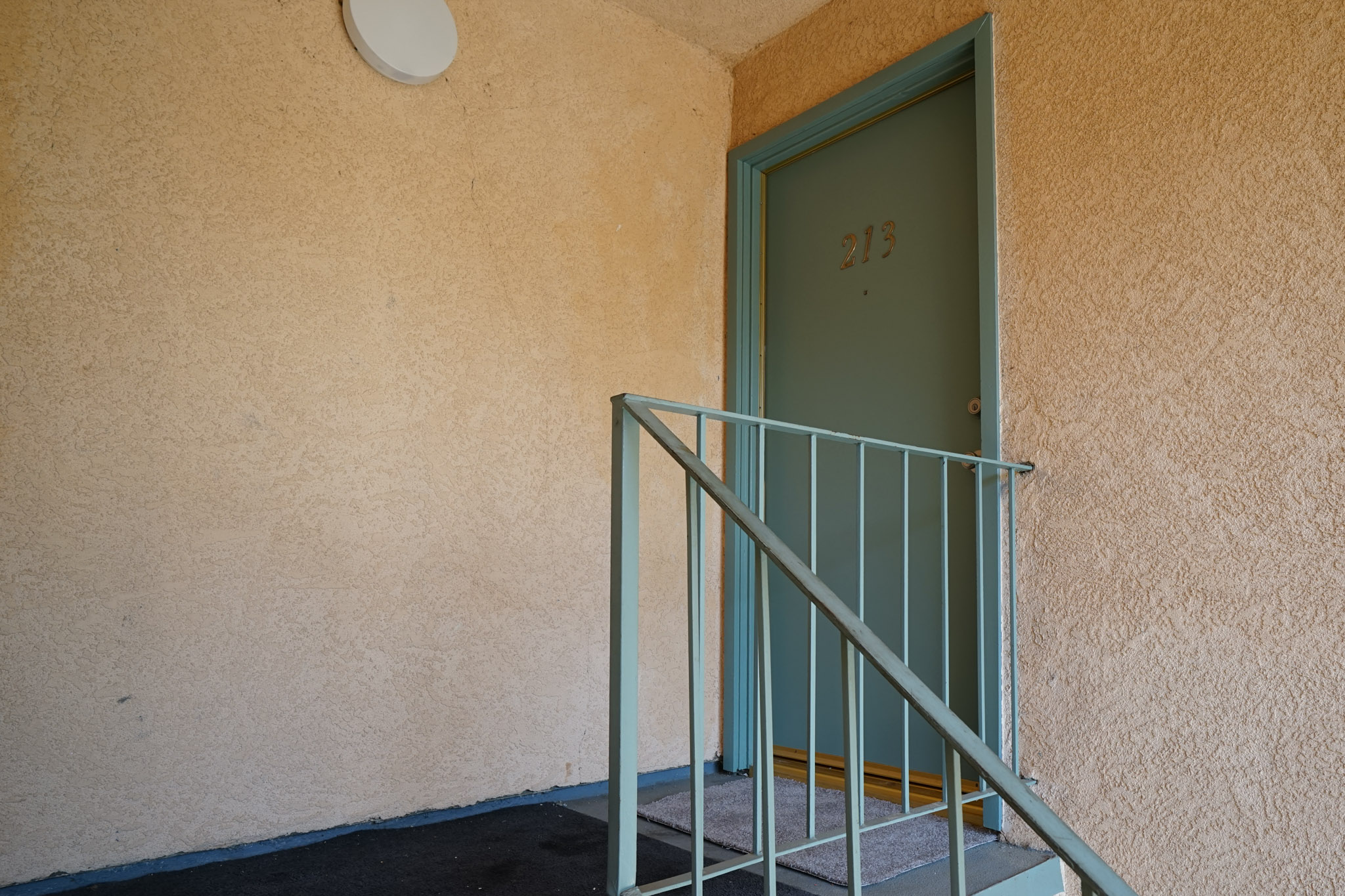 View of a unit's door that has a railing on the side.