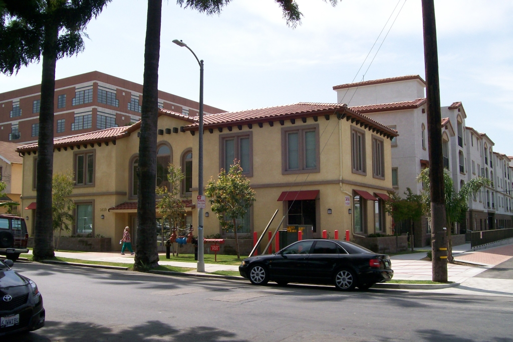Street view of yellow 2 story apartment with grass, sidewalk and palm trees in front