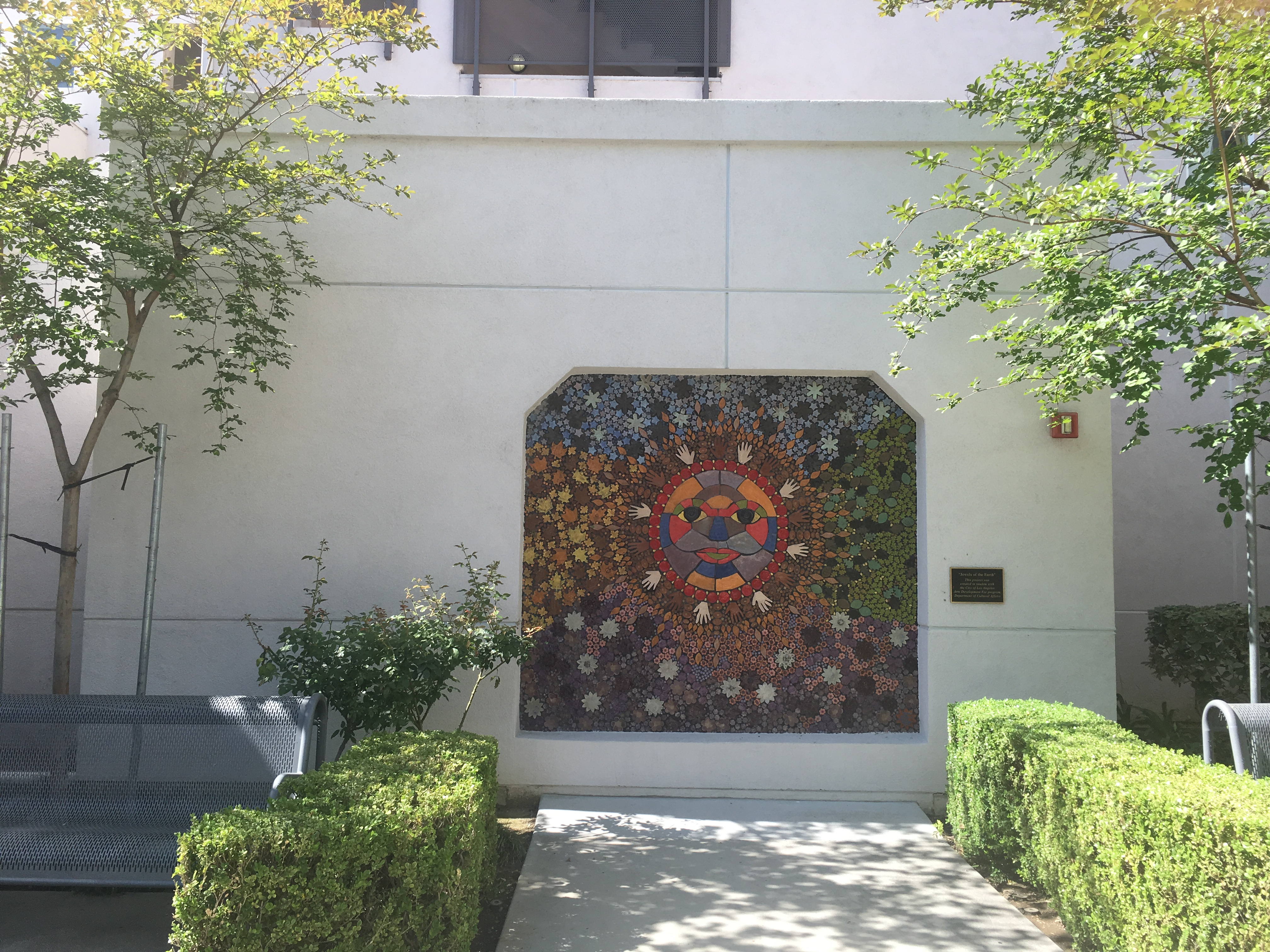 Front view of the court yard, a beautiful colorful mosaic art on the wall, well trimmed bushes on each side, gray iron mesh benches on each side.