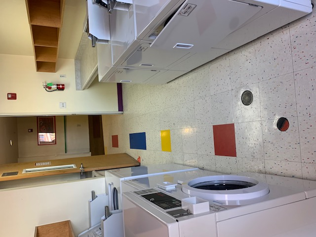 Laundry room consisting of two top-loading washers, one front-loading washer, three dryers, a folding counter, and cubbies mounted along the wall.  All machines are quarter operated.