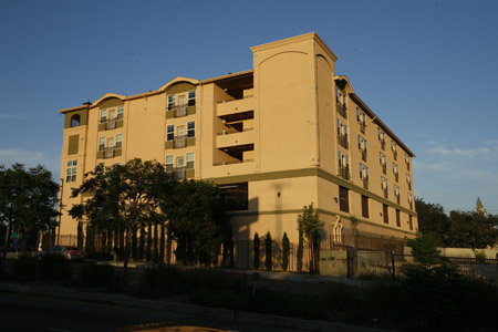 Side view of a four story mustard yellow building, multiple windows some with balconies, trees around the gated building.
