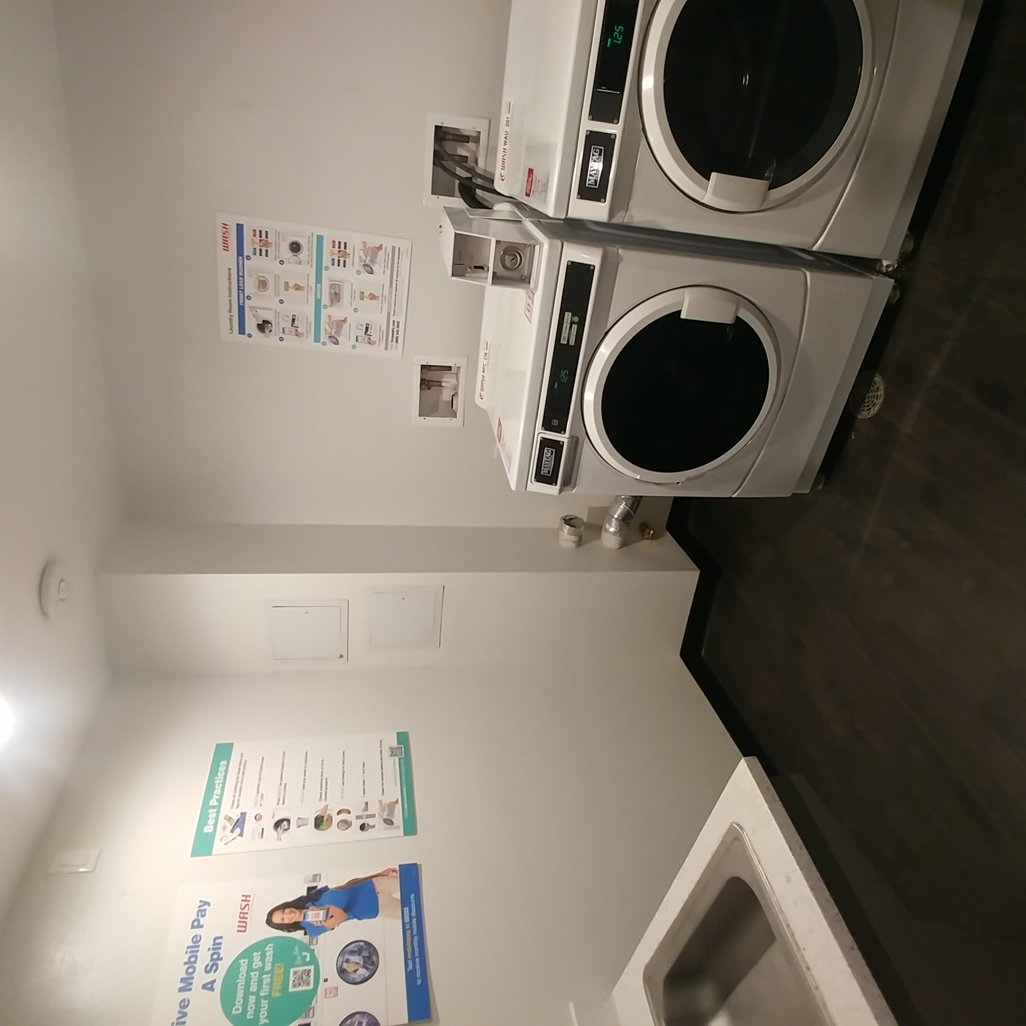 Panama Apartments laundry room. image contains two front load washing units, sink, and operating signs posted on wall
