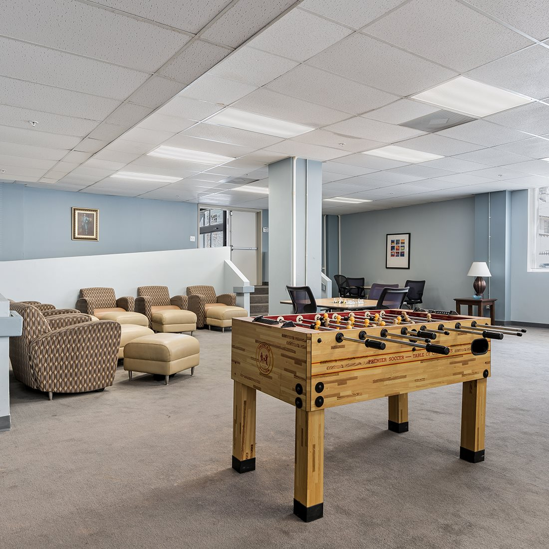 Community room with a foosball table, two round tables with chairs, and multiple sofa chairs. Room has stair and ramp access. Floor is carpeted.