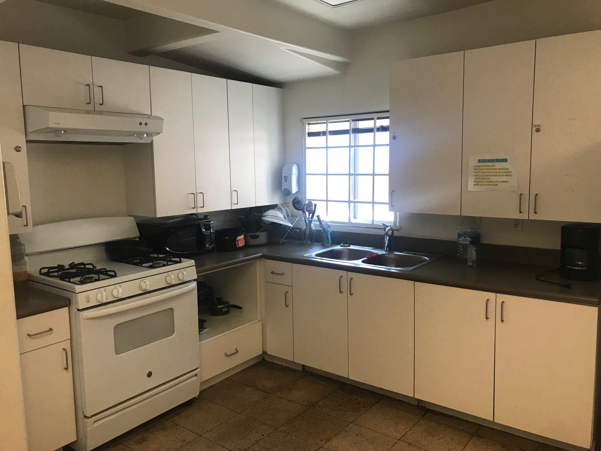 Left side view of a kitchen, white pantry, white stove with oven and under cabinet range hood, black microwave, pots, dishes, gallon of water, cooffe maker, soap dispenser, white window.