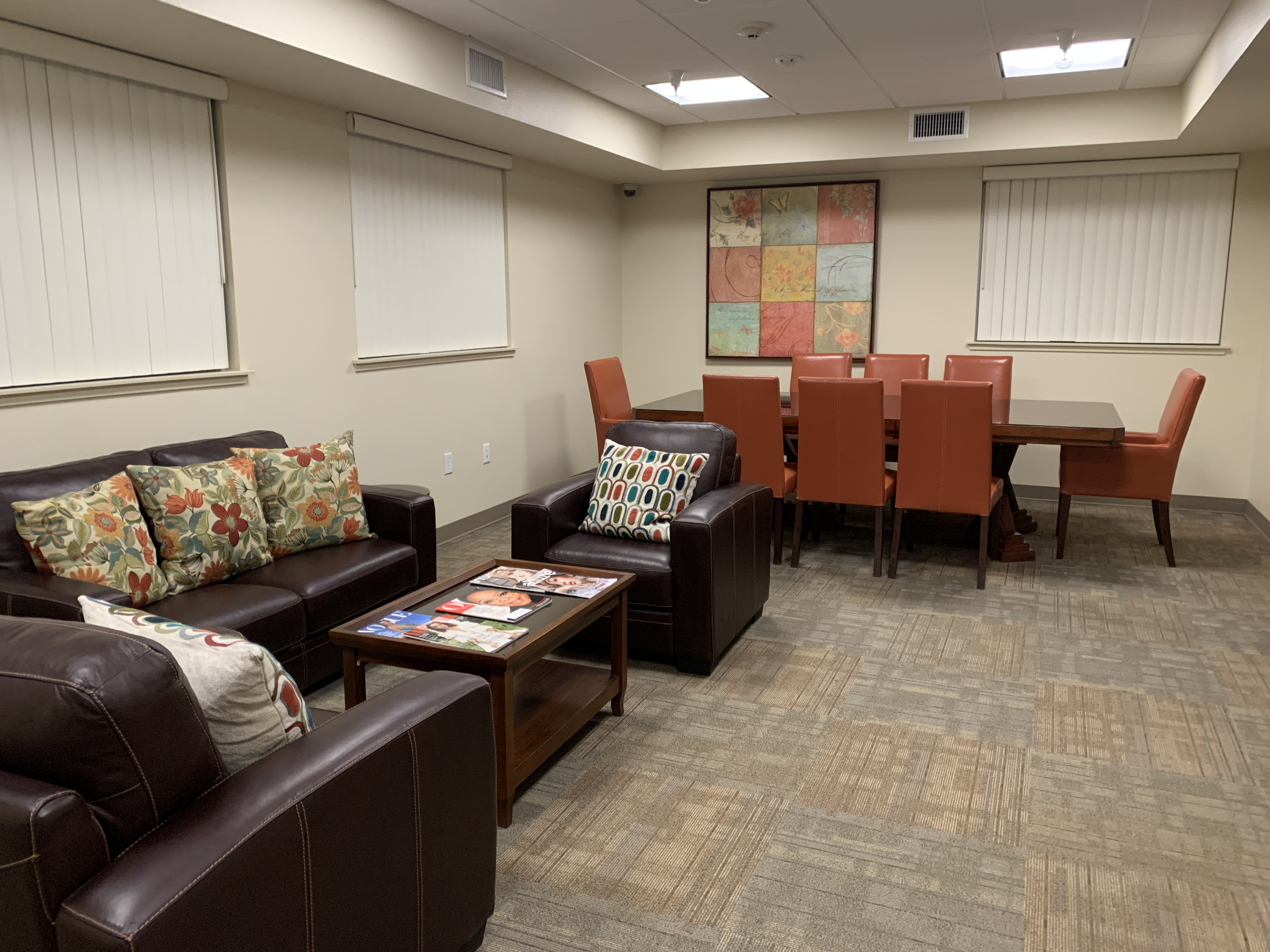 Conference room with a couch, two sofa chairs, a coffee table, and a conference table.