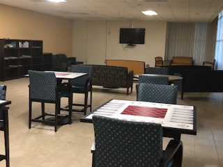 Interior viewo of a community room at Vermont Seniors. Square tables and chairs with a checker board painted on each table