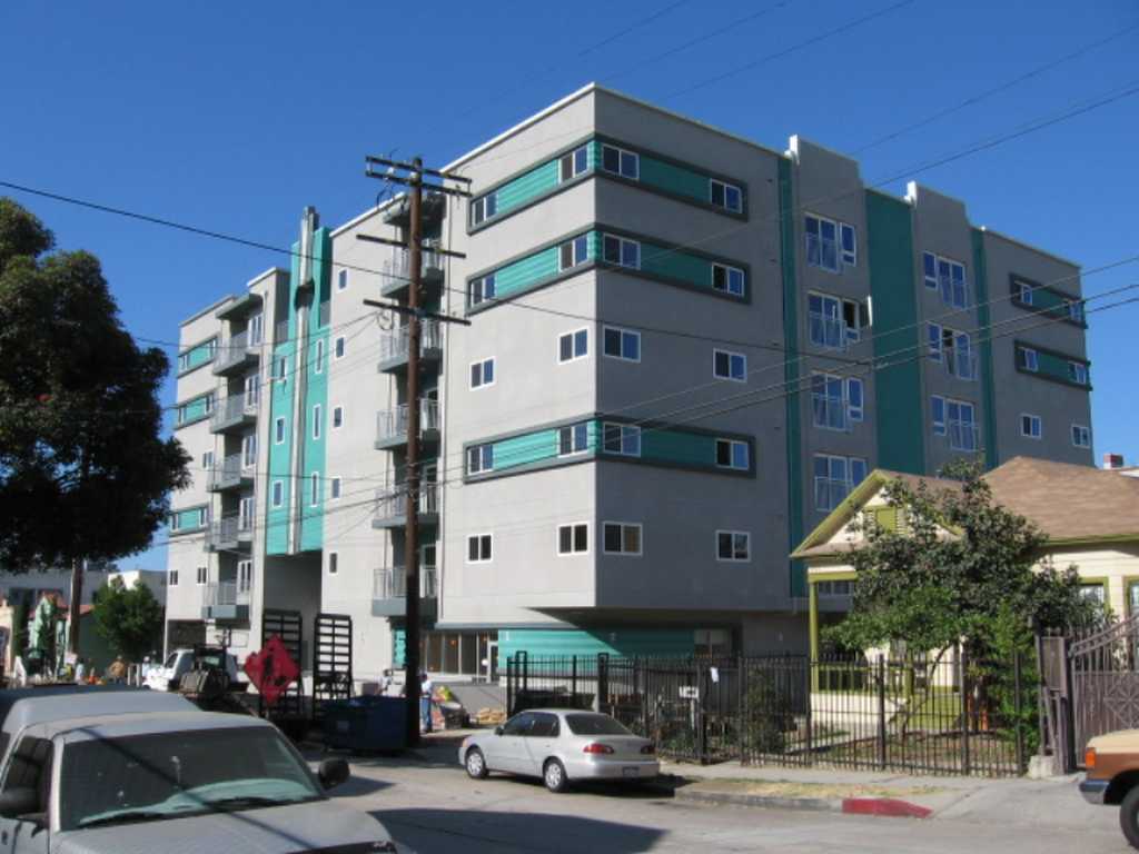 Street view of multi-level building. Building is grey with accents of blue and around windows. Select units with balcony access.