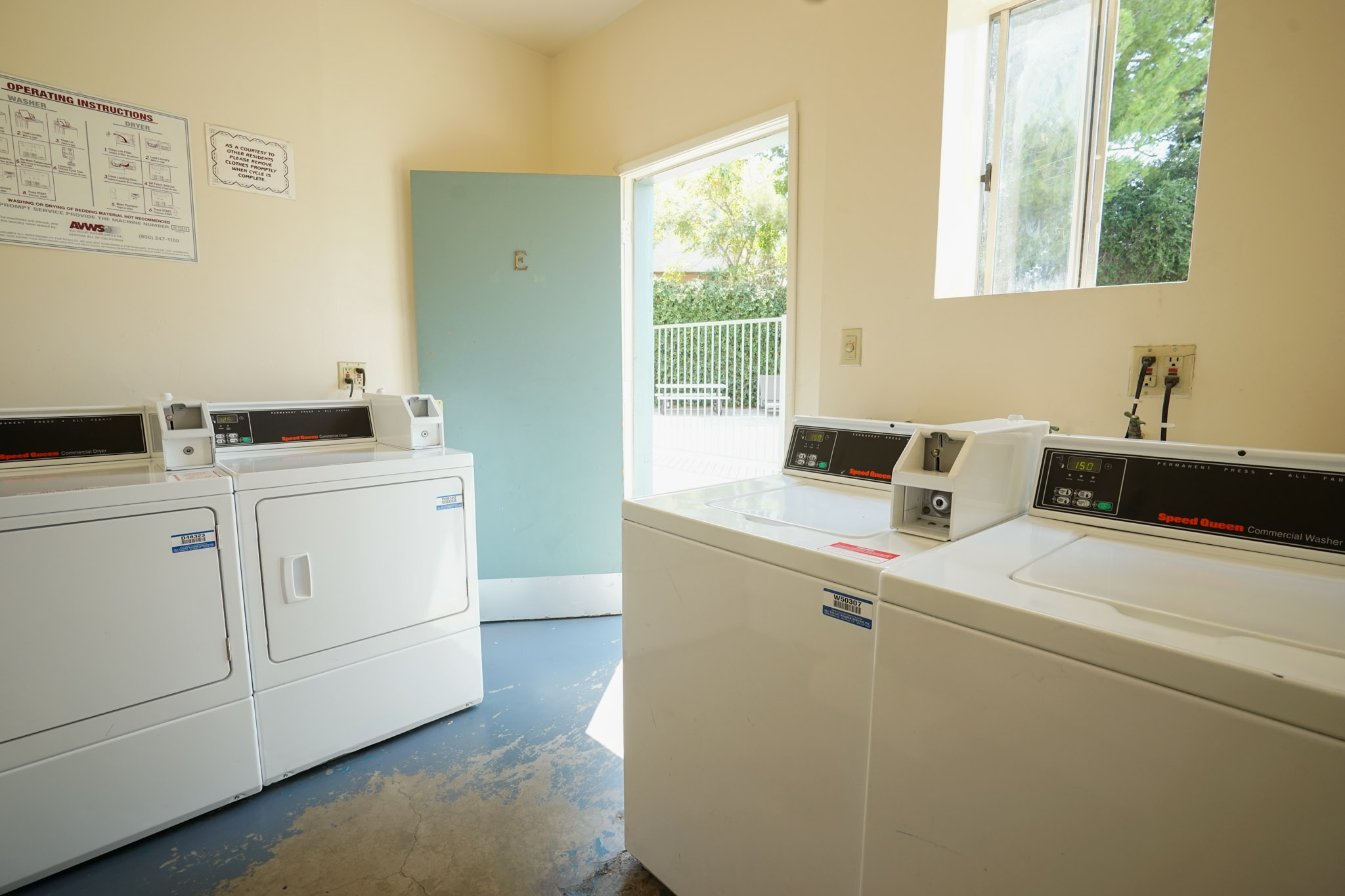 Laundry room with four machines visible. There is an operating instruction sign posted on the wall, and a sliding window.