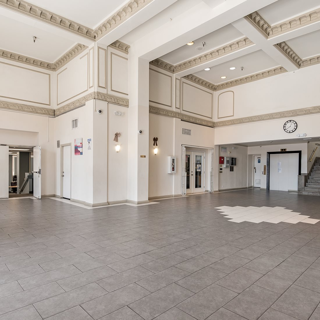 Spacious lobby area with an elevator and a staircase. This area has high ceilings, and security cameras.