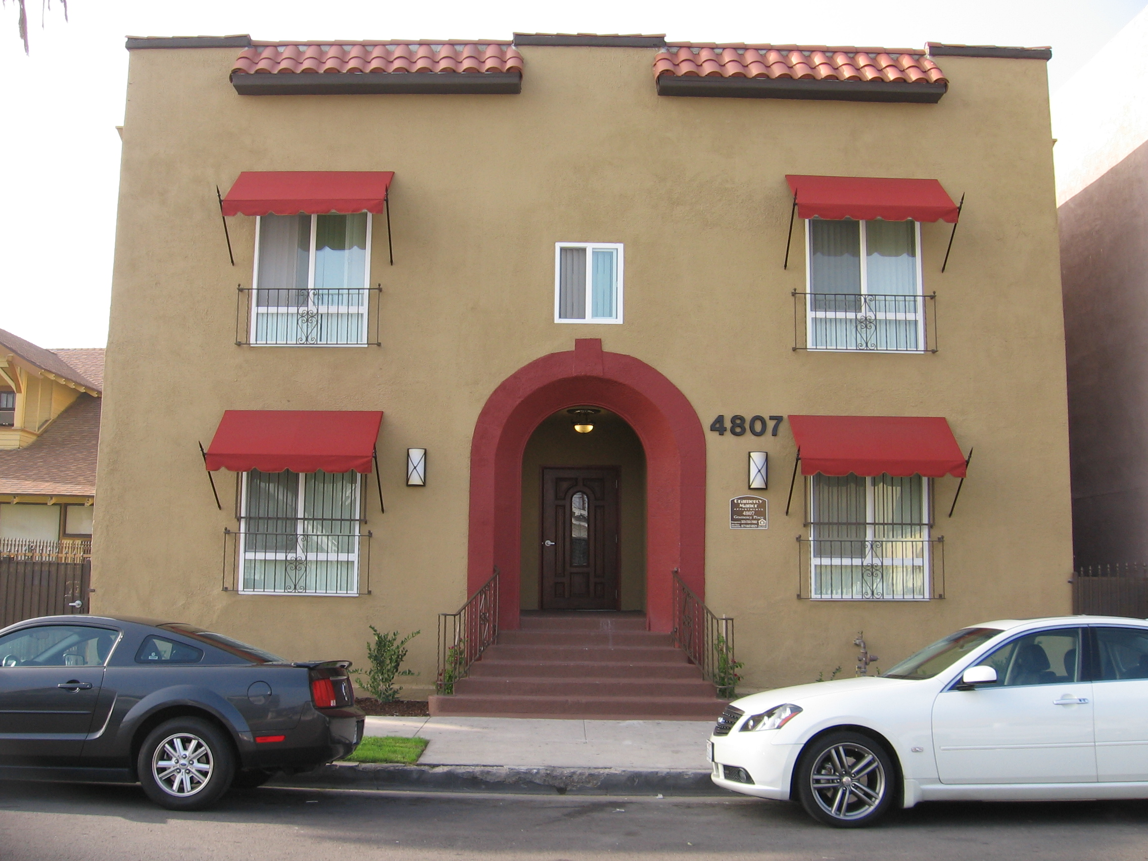 Front view of a light brown two story building, four windows with red shade and mini iron security bars, white outdoor light on each side of the entrance, building number on the right side, building name and address sign on the right side, six burgundy st